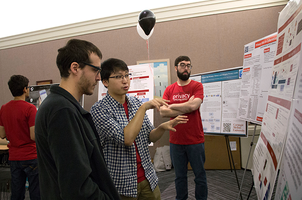 Student explaining his research poster