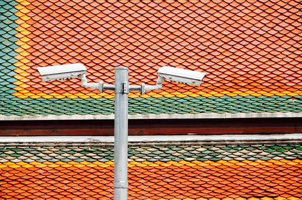 Surveillance cameras pointing down in front of orange tile background